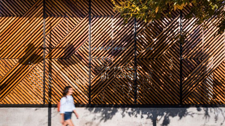 Wooden slats arranged to create a houndstooth pattern cast shadows across this cafe in Dallas by Official, which also designed a cocktail bar at the back.