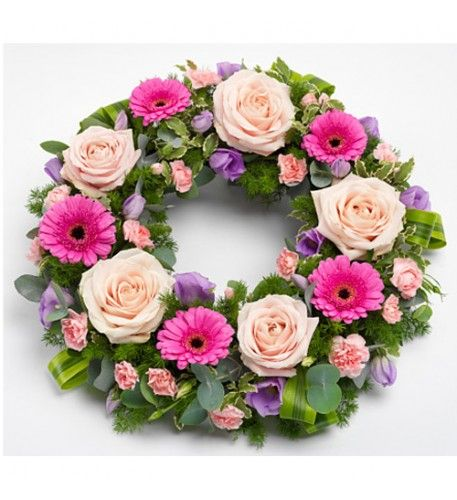 A pretty pink wreath featuring Roses, Germini and Carnations with lilac Lisianthus and mix of luscious green foliage.