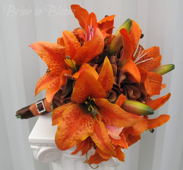 "Tiger lilies are "" the symbol of wealth and pride"". This vibrant orange & rust / brown tiger lily Wedding bouquet is a one of a kind Bride in Bloom Wedding design. Bouquet is designed with the finest quality large orange tiger lilies, small red / orange lilies with rust hydrangea, framed with curly willow. Handle treatment has a shear burnt orange ribbon wrap with brown satin sash ribbon, finished with a sparkling square rhinestone buckle. Bouquet measures 8"" ( 20 c…"