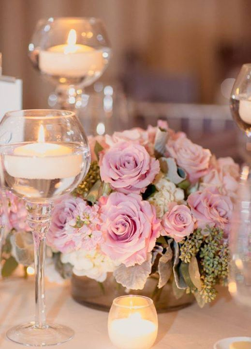 Centerpieces don't need to be large -here a small, romantic arrangement of pink roses is surrounded by vanilla votives and floating candles ~ http://www.modwedding.com/galleries/reception-decor/