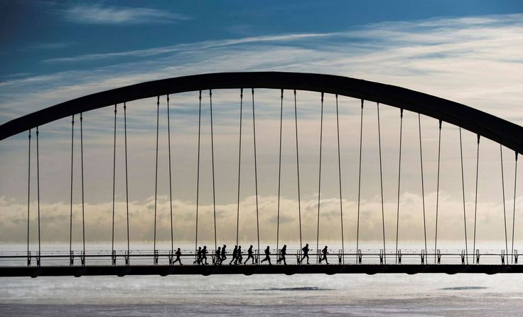 """A group of joggers run across the Humber Bay Arch Bridge during extreme cold temperatures in Toronto, February 16, 2015. Toronto experienced some of the coldest weather of the year reaching -25C (-13F) on Sunday, as Environment Canada lifted its """"extreme cold weather alert"""" Monday when temperatures warmed to -13C (8.6F), according to local reports."""