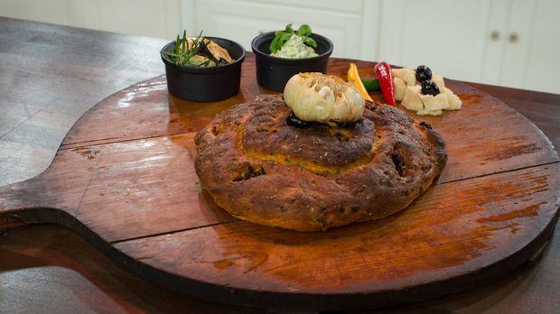 Sonja genießt ihr Antipasti-Picknickbrot sonst immer mit ihrem Mann auf gemeinsamen Wanderungen. Heute darf die Jury von der mediterranen Kombination aus getrockneten Tomaten und Oliven mit Basilikum-Butter-Dip kosten. Das Rezept dazu gibt es unter dem Video.