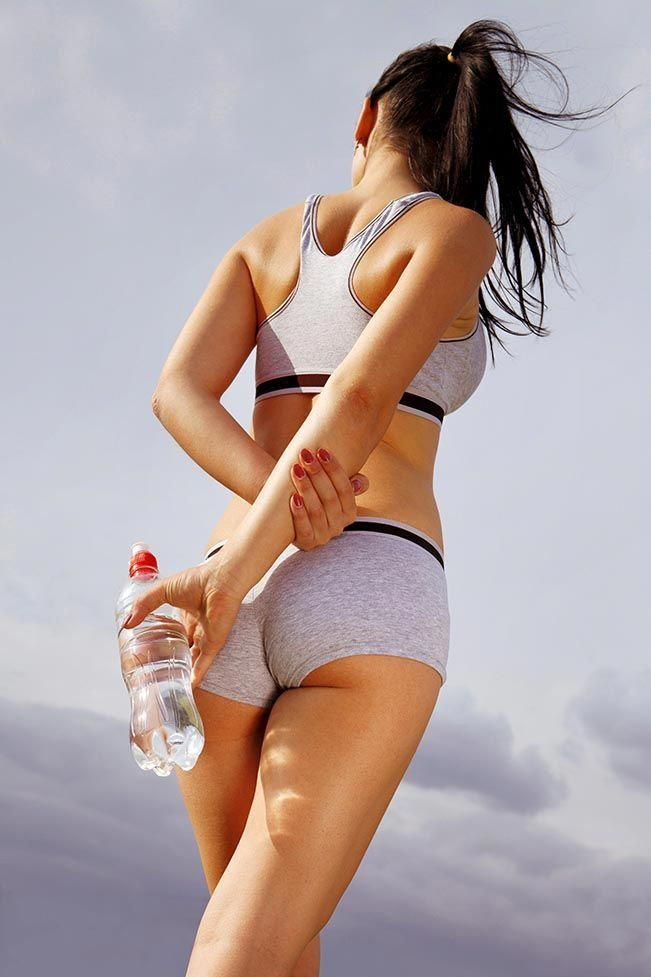 beautiful back of athletic woman that holds bottle of water. Royalty-Free Images…