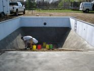 A concrete and vermiculite mixture called pool base is laid down on the floor of the pool and foam is applied to the walls!