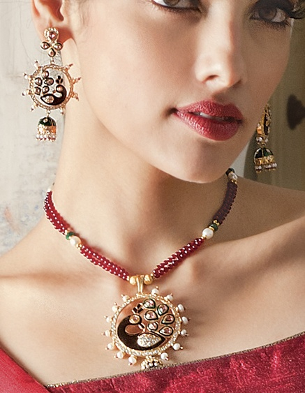 Necklace and earrings in gold polish with cubic zircon and red and green meena work attached with red and green beads mala by Benzer priced at $179. Buy online at www.benzerworld.com