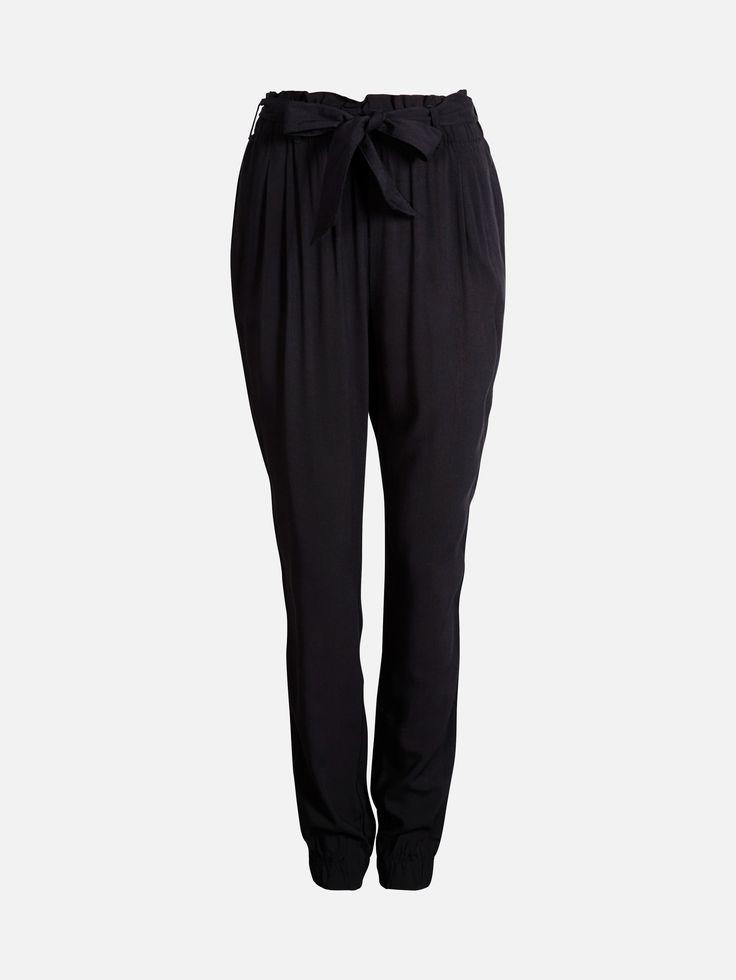 En løstsittende bukse i vevet viskose med strikk og knytebelte i midjen. Buksen har høyt liv, to lommer foran og rysjekant øverst.  Sort