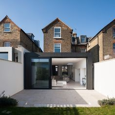 Light garden walls and patio, dark extension and sliding doors - beautiful contrast with existing brick. CLICK http://www.hollandgreen.co.uk/house_extensions#.VABdmDJdU7k to see if you could do something similar