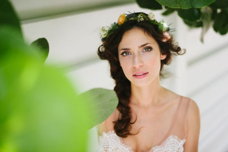 the bride wears her flower crown made of peach ranunculus, blue thistle, white wax flower, white spray rose, blue nigella.