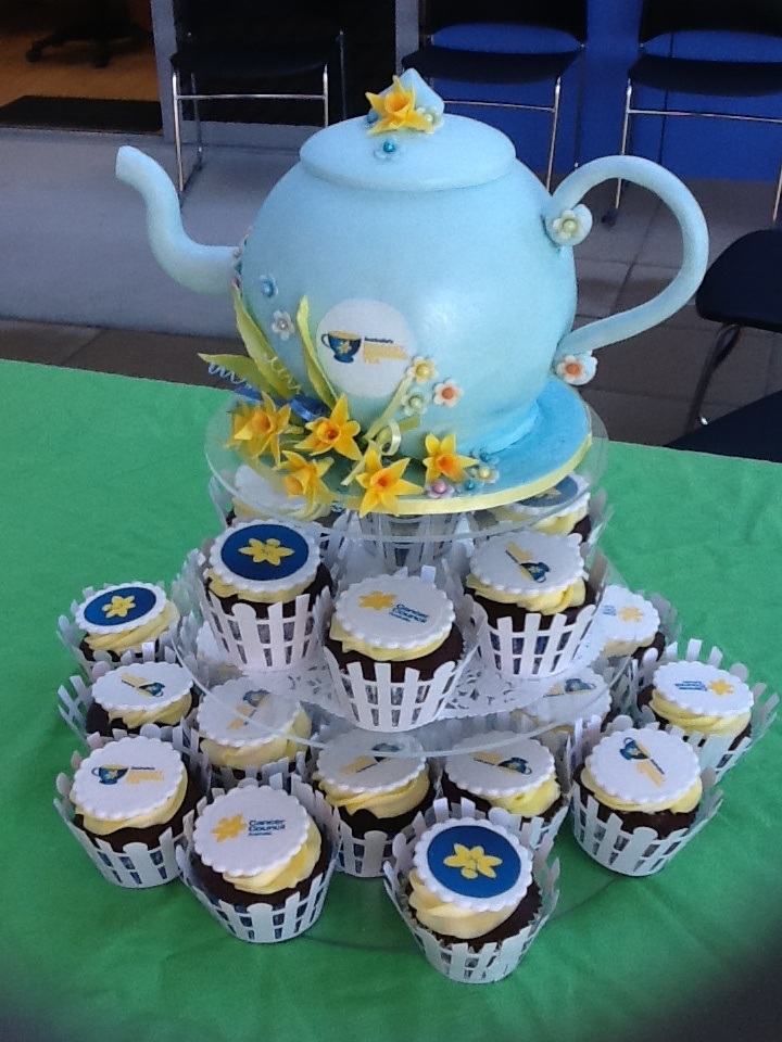 Teapot cake with matching cupcakes for Cancer Council Biggest Morning Tea. Red velvet teapot with cream cheese frosting, fondant covered. Handmade daffodils and blossoms. Red velvet cupcakes with raspberry cream filling and cream cheese swirl. Edible image on fondant scalloped disc