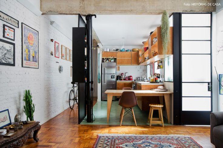 Cozinha integrada com armários de madeira e piso de ladrilho hidráulico.