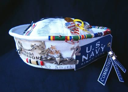 Navy enlisted cover (white hat) decorated with medals, ribbons, insignia and other items. Image from an old blog about military crafts.