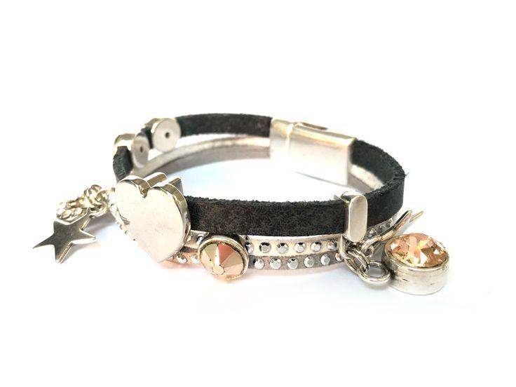 Uniek handgemaakte armband met magneetsluiting in de kleurstelling zilver, wit, donker grijs. Zilver groot hart. Gecombineerd met peach kleur swarovski steen en zilveren bedels. Hanger en facet kristallen