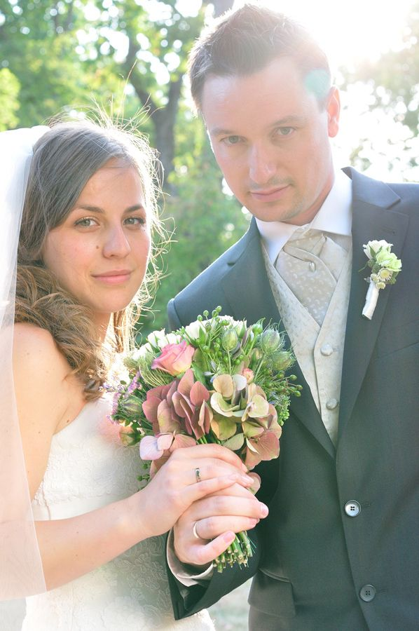 bride and groom showing the rings and flower bunch