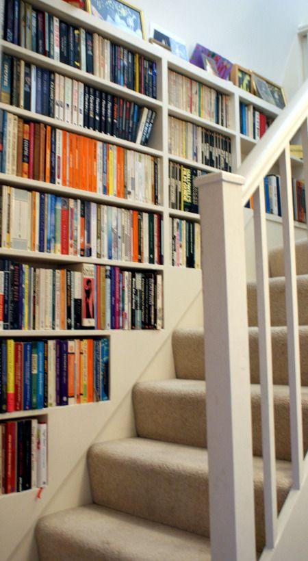 Bookshelf wall up stairway.