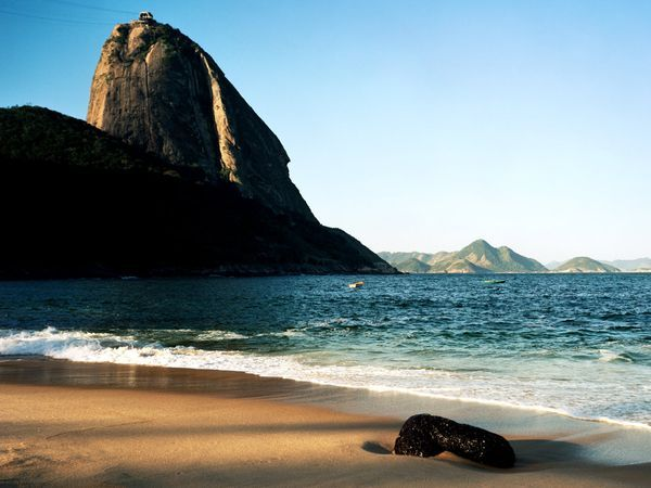 Sugarloaf Mountain Photograph by Zoran Milich/Masterfile Sugarloaf Mountain juts into the sky over a beach in Rio de Janeiro, a city known for its magnetic beach culture.