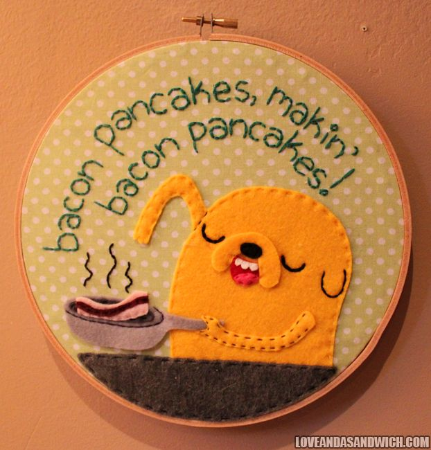 Bacon pancakes makin' bacon pancakes, take some bacon and I'll put it in a pancake.  Bacon pancakes that's what it's gonna make, bacon pancaaaaakes!Now it's stuck in your head.Embroidered/appliqued hoop of Jake singing the bacon pancake song!