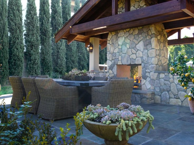 Guests at this transitional outdoor cabana space can stay warm by the two-sided fireplace before enjoying dinner at the Restoration Hardware dining set. Planted succulents, a lemon tree and roses enliven the texture and add to the richness of the scenery.
