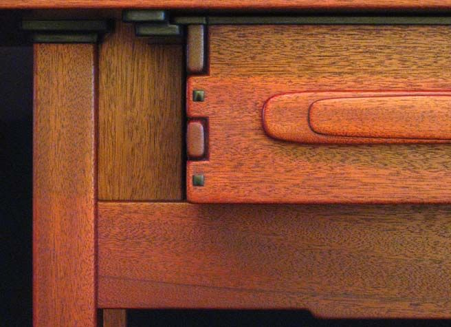 Greene and Greene reproduction table by Jeff Grainger Studio. Mahogany with dyed finish, finger jointed drawers on ebony runners, hand-carved handles. Brass pins secure drawer runners. (detail)
