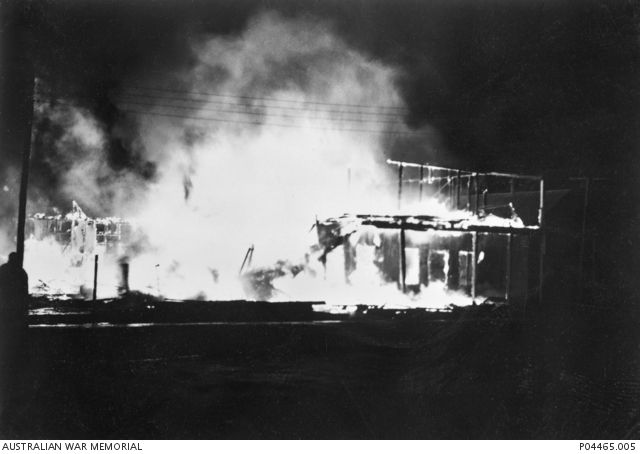 Blazing buildings light up the night, after the bombing of Darwin by Japanese…