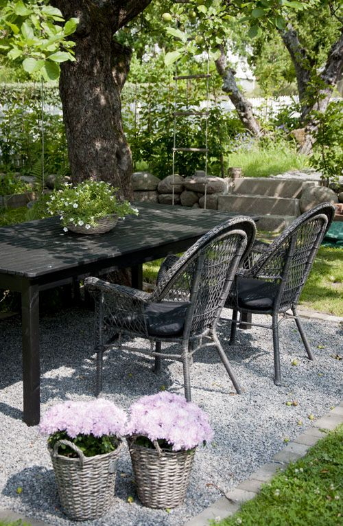 Here's proof that an outdoor dining area as a part of your landscape design doesn't have to be elaborate. This table with wrought iron chairs has been set in gravel (nice touch - no mud, no weeds underneath) under a shady tree, and accented with potted flowers in baskets. I can see this in our new backyard beond the pool.