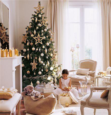 Salón navideño con chimenea y niña sacando adornos
