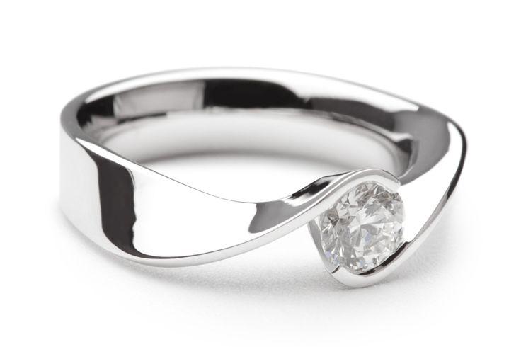 Sierlijk vormgegeven verlovingsring waarbij de scheen van de ring tordeert. De twee uiteinden van de verlovingsring vouwen zich om de diamant, waarbij de diamant aan twee zijden vrij staat. De verlovingsring New York is uit te voeren met een diamant formaat naar keuze.
