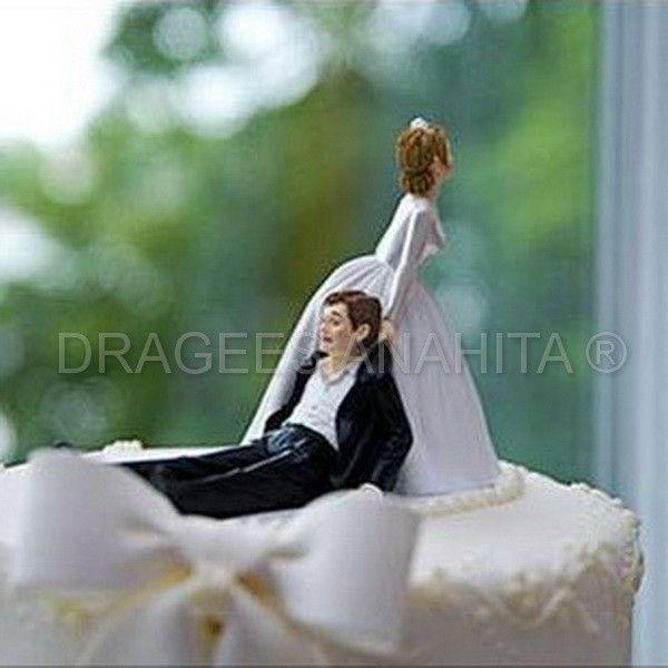 Une figurine couple de mariés à placer sur le gateau de votre mariage, une mariée qui tire par le col son futur époux, parce que l'humour est primordial pour une cérémonie de mariage.