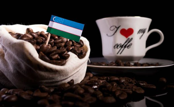 uzbekistan flag in a bag with coffee beans isolated on black