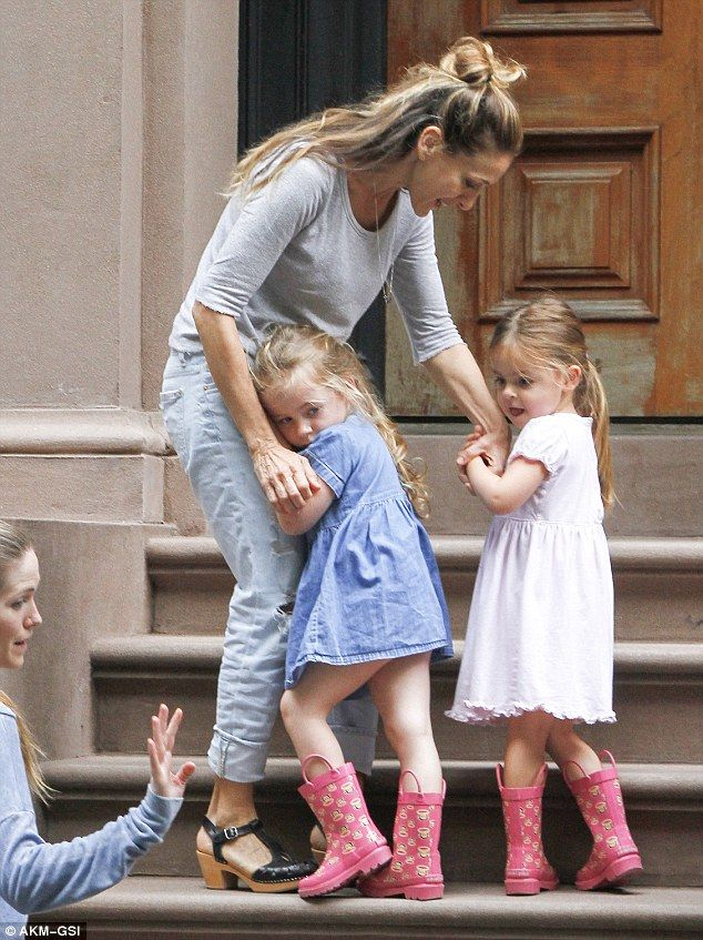 Mommy's little girls: Sarah Jessica Parker's adorable twin daughters Marion (in blue) and Tabitha (in pink) cuddle up to their mom as they get ready for a family outing in Manhattan on Saturday