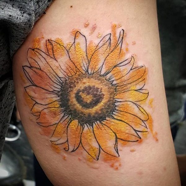 Sunflower tattoo design in watercolor theme. The colors are seem to be splashed on the sunflower making the design look laid back abut at the same time artistic.
