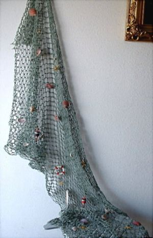 Fish Nets with Shells and Decorations NDHLK14. Algae green 5 foot x 10 foot net with sea shells, floats and accessories like mini floats, fish bobbers, life preservers and other nautical treasures.  Great for nautical theme parties, creative interior designs, outdoor patio & garden use, sea life & seashell decor displays, restaurant decor, kids rooms and wall hangings.