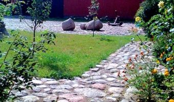 Red Bird Farm, showing cobbled inner courtyard and abundant flowers in summer.