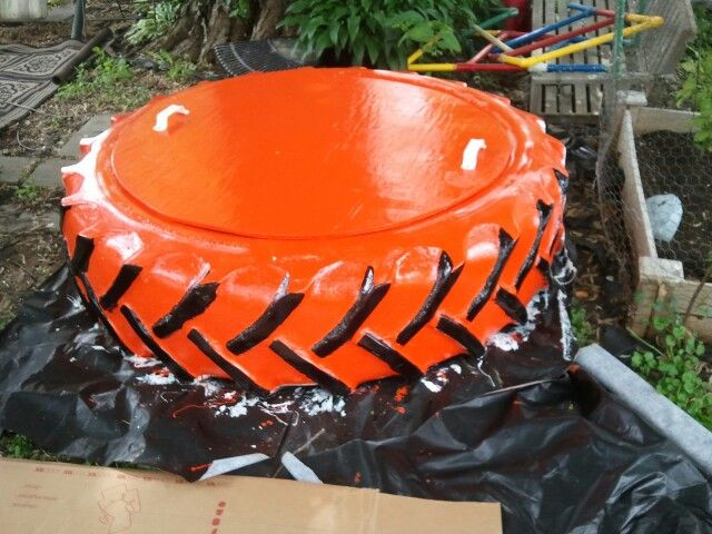 Orange and black tractor tire sandbox with lid.  Just have to add my grandson, Oliver, handprint on the lid.