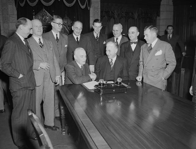 Newfoundland and Canadian Government delegation signing the agreement admitting Newfoundland to Confederation. Prime Minister Louis St. Laurent and Hon. A.J. Walsh shake hands following the signing of the agreement / Signature, par les délégués de Terre N   by BiblioArchives / LibraryArchives