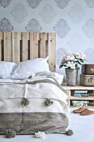 Même concept de tête de lit avec une palette fixée à la verticale qui forme un ensemble avec la table basse palette elle aussi faite de 2 palettes au même aspect brut d'origine simplement superposées en guise de table de chevet.
