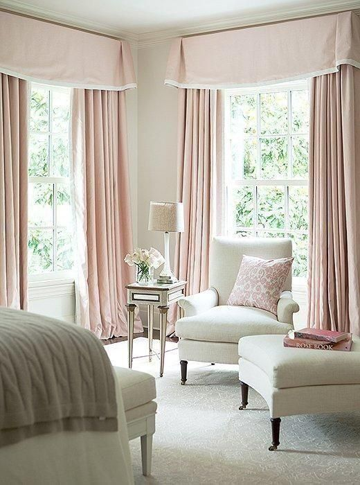 Sophisticated and feminine pale pink bedroom with floor to ceiling pink curtains and all-white furnishings.