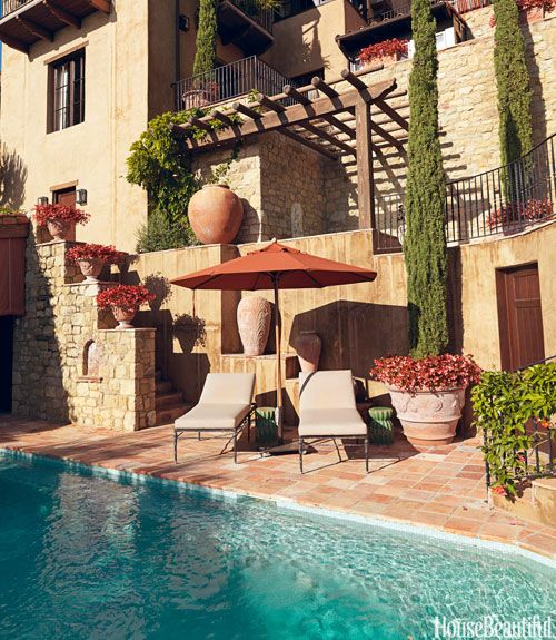 At a Southern California house decorated by Michael S. Smith, the homeowners can stretch out by the pool on Michael Taylor's Montecito Sun Chaises, under an orange Sunbrella umbrella.   - HouseBeautiful.com
