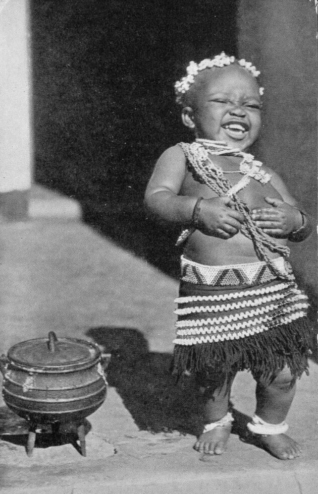 Africa   Child laughing next to a three leg cooking pot. South Africa.   Scanned old postcard. ca. 1940s