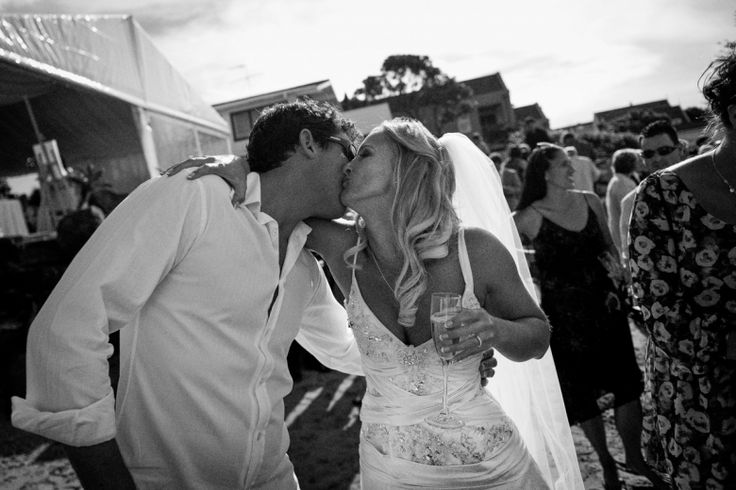 Bride kisses a guest at a wedding at home at Milford beach, Auckland. Black and White.  beguiling fine art family photographs for the walls of the most discerning clients homes. We specialise in wedding and family portrait photography, and supply prints on the highest quality media, framed in beautiful conservation standard frames. We are a high end studio located in the beautiful city of Auckland, New Zealand.