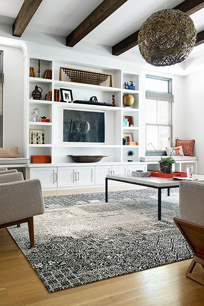 The open beams, our Kensington Garden rug and pops of orange décor give this living room an effortlessly cool vibe.