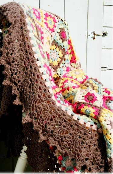 Granny squares with beautiful edging, and I love the neutral, calm brown juxtaposed to the riot of color.