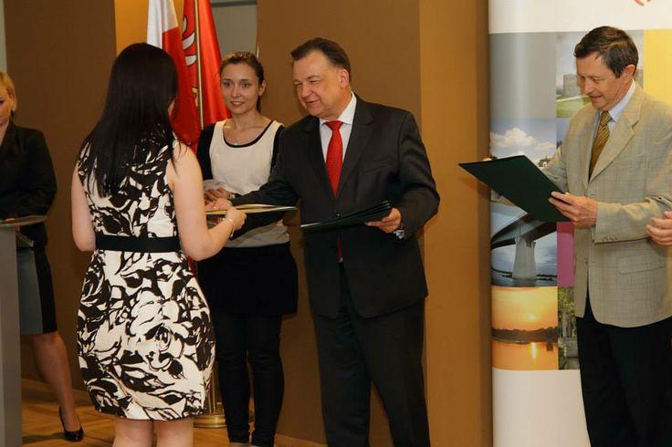Reprezentantka Fundacji odbiera z rąk Marszałka Województwa Mazowieckiego  dyplom uznania.