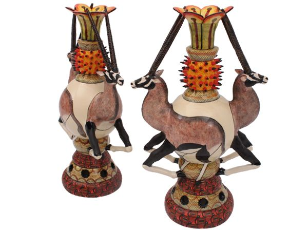 This statuesque pair of candlesticks feature oryx, whose magnificent horns seem to protect the holder against the spiky aloe flowers which adorn the candlestick necks. Created by Sabelo Khoza and painted by Jabu Nene.
