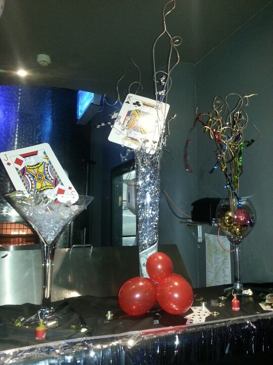 www.la-occasion.com - James Bond Themed Party  Tall Conical Vase filled with silver shimmer shredded paper with dollar bill wrapped at the bottom of the vase.  Silver stick and XXL playing card placed inside the vase.    Martini Vase with clear diamond stones with XXL playing card.