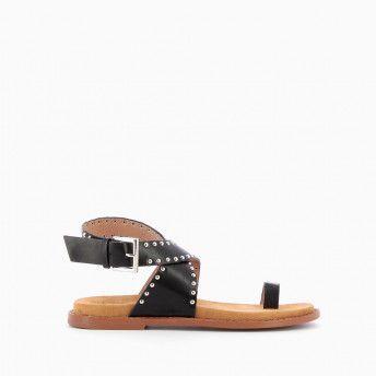 Sandales plates noires effet cuir décorées de petits clous ronds argentés. Brides croisées à la cheville et passe-pouce. Fermeture à boucle argentée.