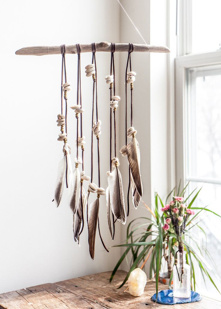 This gorgeous wall hanging is made with driftwood collected on the California coast, adorned with leather fringe, cowrie shells and beautiful feathers. Driftwoo