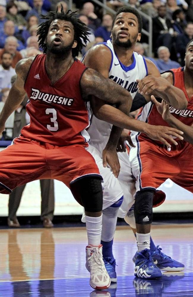 Saint Louis' Dwayne Evans, center, can't get through the defense of Duquesne's Dominique McKoy (3) and Jerry Jones (5) during the second half of an NCAA college basketball game, Thursday, Feb. 27, 2014, in St. Louis. Duquesne beat Saint Louis 71--64