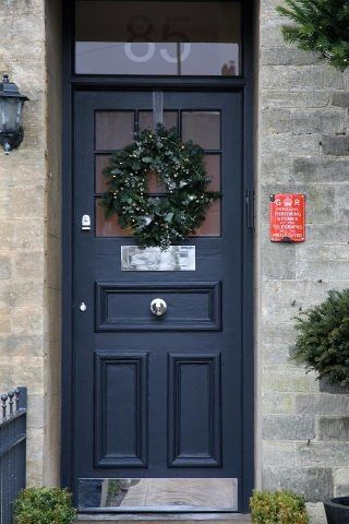 This Festive wreath looks very smart hanging on this door against a front door painted in Railings by Farrow & Ball. The drops of white on the wreath really bring the whole door to life.