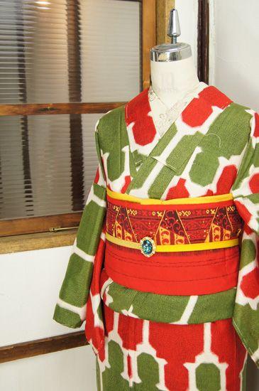 アイボリーに、ハーブグリーンと赤で、西洋の飾り枠のような装飾模様が織り出された銘仙袷着物です。