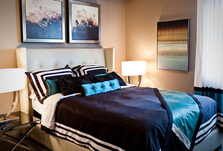 This elegant, ocean escape style bedroom was achieved through Contemporary & elegant furniture selections and bright splashes of color that reflect the ocean. Instead of selecting beach themed artwork, try finding artwork that reflects the colors of the ocean, and utilize that same color palette in your toss cushions and throw blankets. Notice how we even carried it through to the drapery, but only in the bottom banding, the key is to select parts of the textiles to bring the color in.
